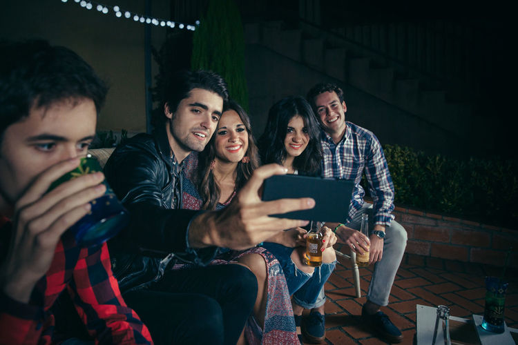 Group of happy young friends drinking and taking a selfie photo with smartphone in a outdoors party. Friendship and celebrations concept. Celebration Friends Fun Happiness Happy Horizontal Young Alcohol Cheerful Drink Entertainment Friendship Group Group Of People Looking Night Nightlife Outdoors Party People Phone Photo Smartphone Smiling Sofa