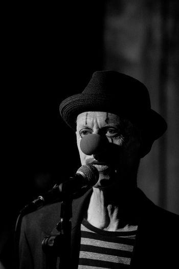 Clown singing while standing in dark