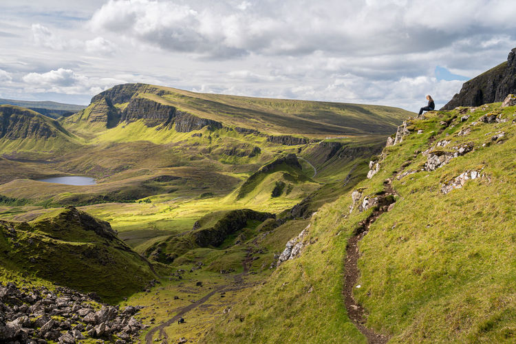 Girl sitting on rock and looking at view of rocky outcrop in the quiraing, isle of skye, scotland