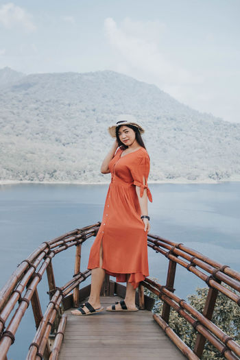 Woman standing on railing against sea