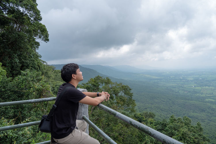 Side view of man looking at landscape against sky