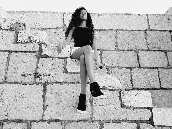 Low Angle View Of Young Fashion Model Sitting Stone Wall