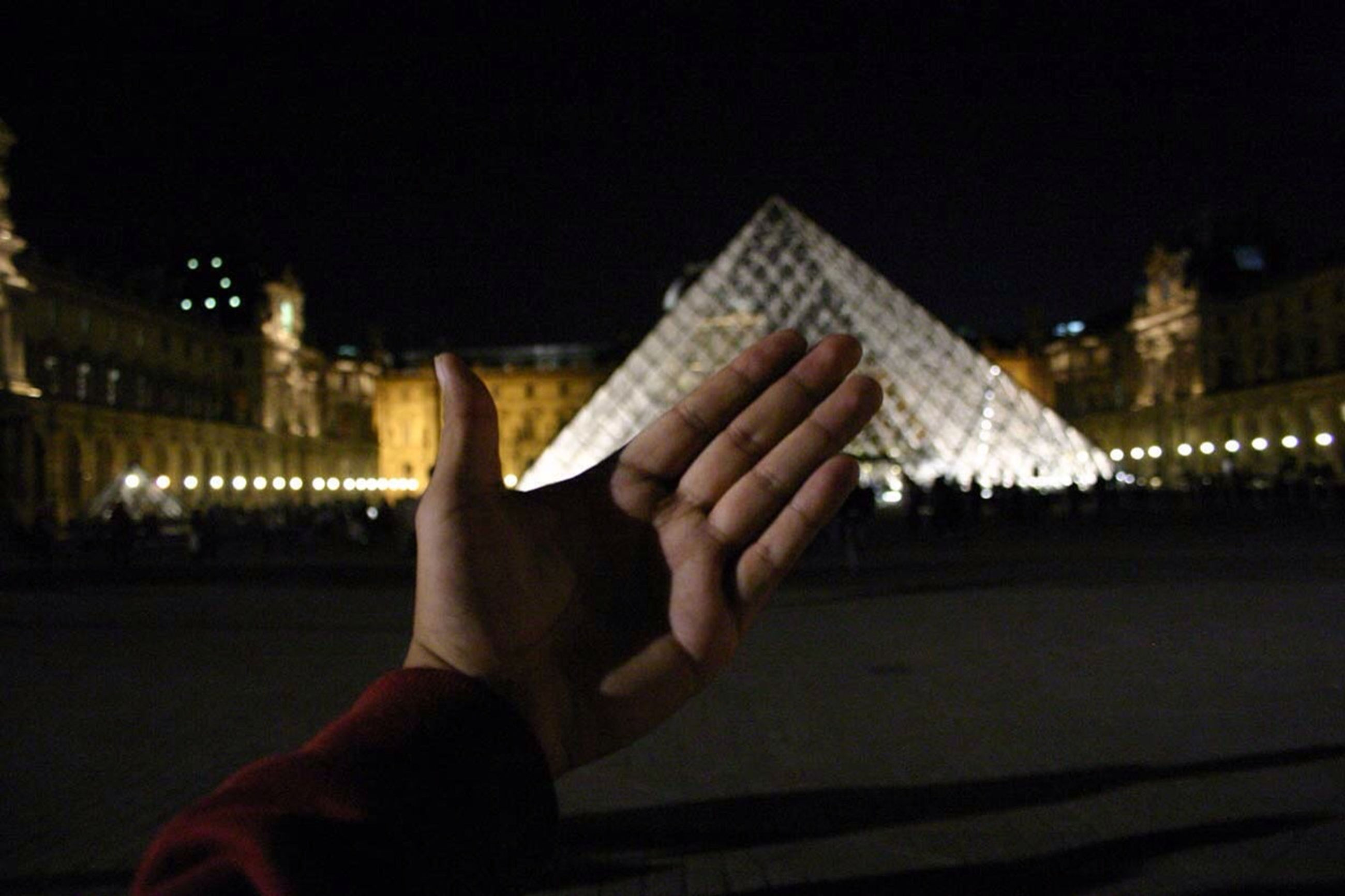 person, night, lifestyles, illuminated, part of, building exterior, leisure activity, cropped, architecture, built structure, holding, personal perspective, unrecognizable person, city, men, human finger