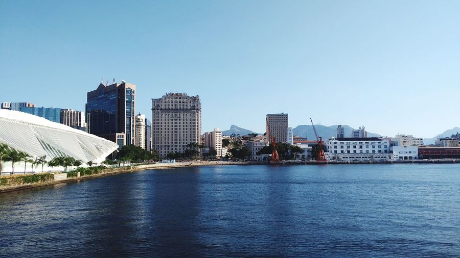 View of buildings by river against blue sky