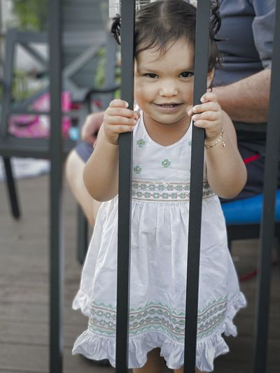 Portrait of cute girl standing by railing outdoors