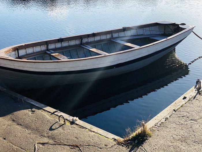 Boat moored on lake against sky