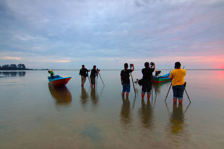 Beach Cloud - Sky Group Of People Horizon Over Water Land Leisure Activity Lifestyles Men Nature Nautical Vessel Outdoors People Photographer Real People Rear View Reflection Scenics - Nature Sea Sky Sunset Transportation Water