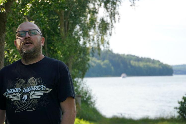 Portrait of mature man standing against lake