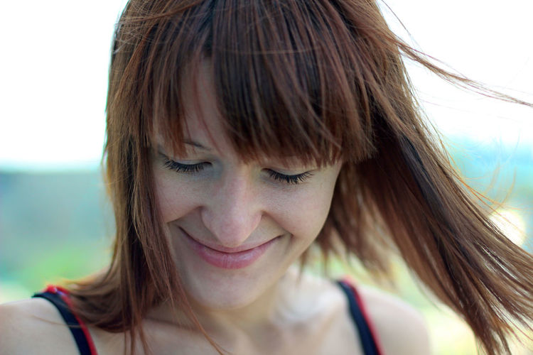 Close-up of smiling woman with eyes closed at beach