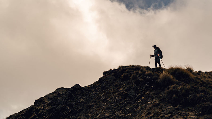 Low Angle View Of Man Hiking On Mountain Against Cloudy Sky
