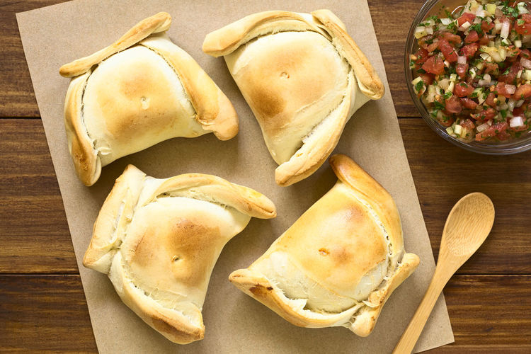 Chilean Empanada, a baked pastry stuffed with meat, with Chilean pebre sauce on the side, photographed overhead on dark wood with natural light Breakfast Chile Chilean  Empanadas Fast Food Filled Stuffed Baked Bread Chilean Food Empanada Empanada De Pino Food Food And Drink Meal Meat Pastry Pasty Pebre Pino Ready-to-eat Salsa Savory Savory Food Snack
