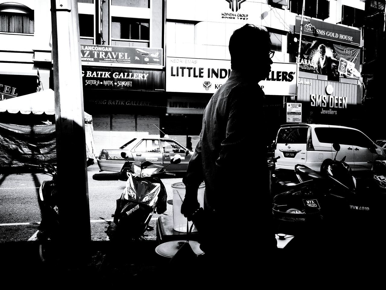 SIDE VIEW OF SILHOUETTE MAN STANDING BY CITY