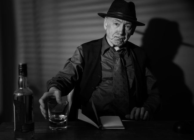 Film Noir reloaded: The dirty old detective in his bureau talking to a new client Acting Adult Hat Suit Tree Alcohol Bottle Detective Drinking Indoors  Monochrome Old Person Old Person Sitting One Man Only One Person Portrait Real People Studio Shot