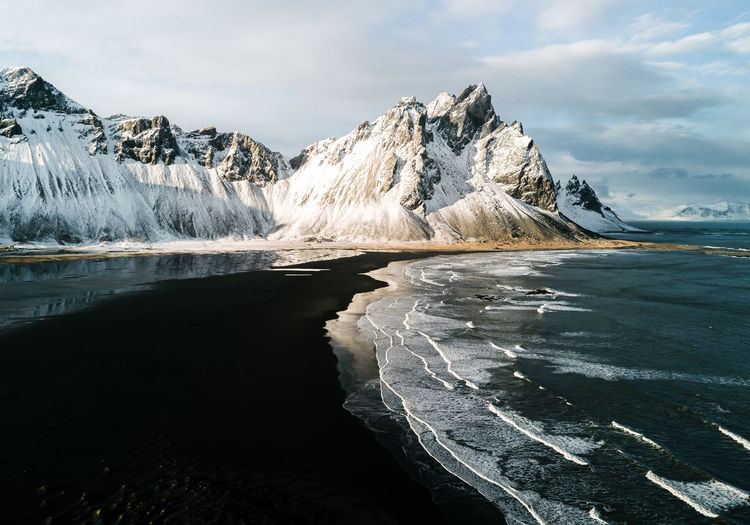 Aerial of Stokksnes beach in Iceland during winter and sunset with mountain in background DJI X Eyeem Iceland Northern Ireland Scandinavia Stokksnes Aerial Beauty In Nature Cold Temperature Day Glacial Iceberg Lake Landscape Mountain Nature No People Outdoors Polaroid Range Scenery Scenics Sky Snow Water Winter Shades Of Winter