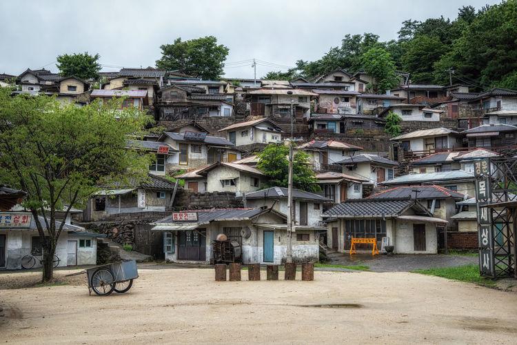 Houses by road against buildings in city