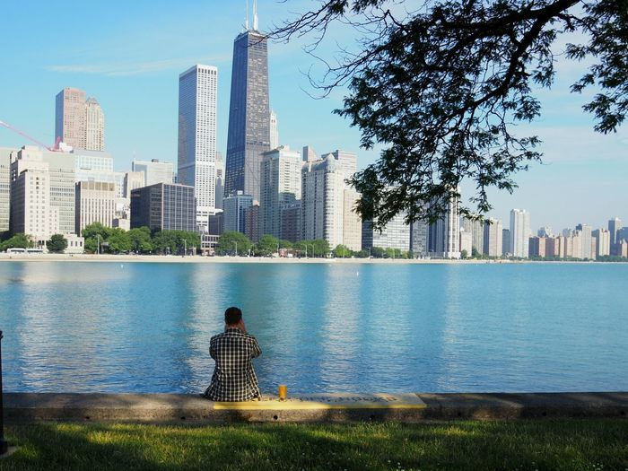Rear view of man sitting by river and cityscape against sky