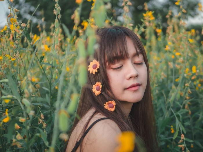Woman wearing flowers amidst plants