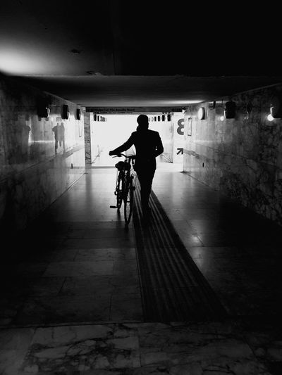 Silhouette man with bicycle in tunnel