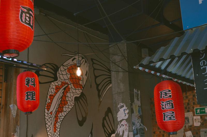 Illuminated lanterns hanging by building