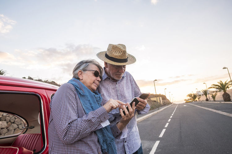 Senior Couple Using Smart Phone While Standing On Road Against Sky