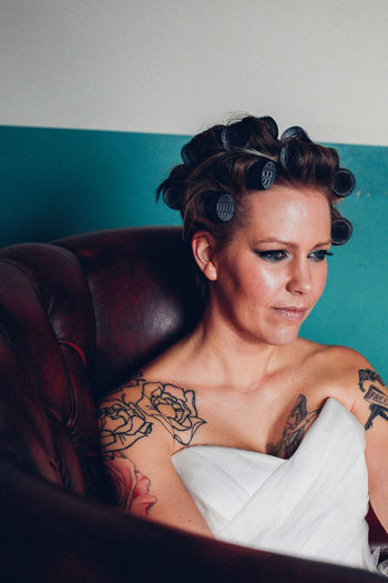 Thoughtful bride sitting on chair at home