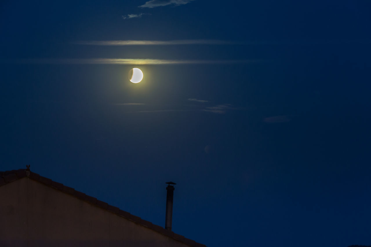LOW ANGLE VIEW OF SILHOUETTE MOON AGAINST BLUE SKY