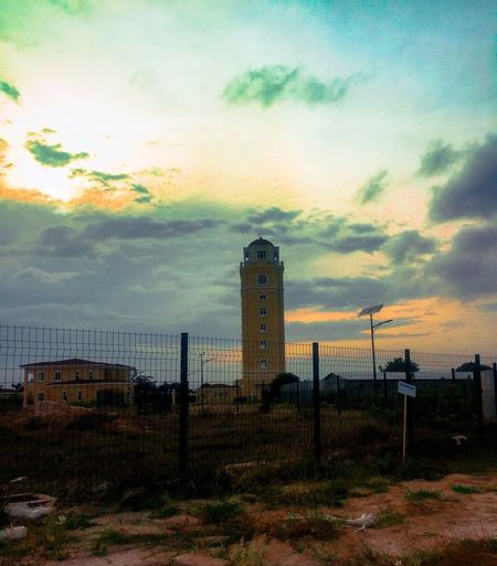 Sun setting beyond dark clouds ⛅️ Dramatic Angles Dramatic Lighting City Street City Street City Tank Orange Color Taking Photos Tower Cloudy Sunset Cloud - Sky Yellow Cloud - Sky Sky Building Exterior Architecture Sunset Built Structure No People Fence Nature Beauty In Nature Outdoors Building Dramatic Sky