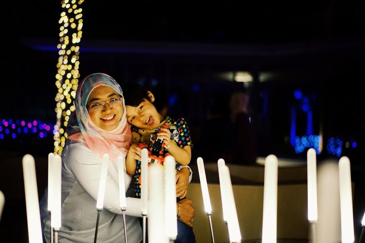 Portrait of mother and son with illuminated lighting equipment at night