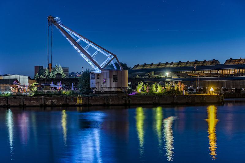 StrandSalonUntertrave Architecture Blue Built Structure City Cityscape Crane Engineering Illuminated Lübeck, Germany Nature Night No People Outdoors Reflection River River Trave Sky Standing Water Tranquil Scene Tranquility Untertrave Water Waterreflections
