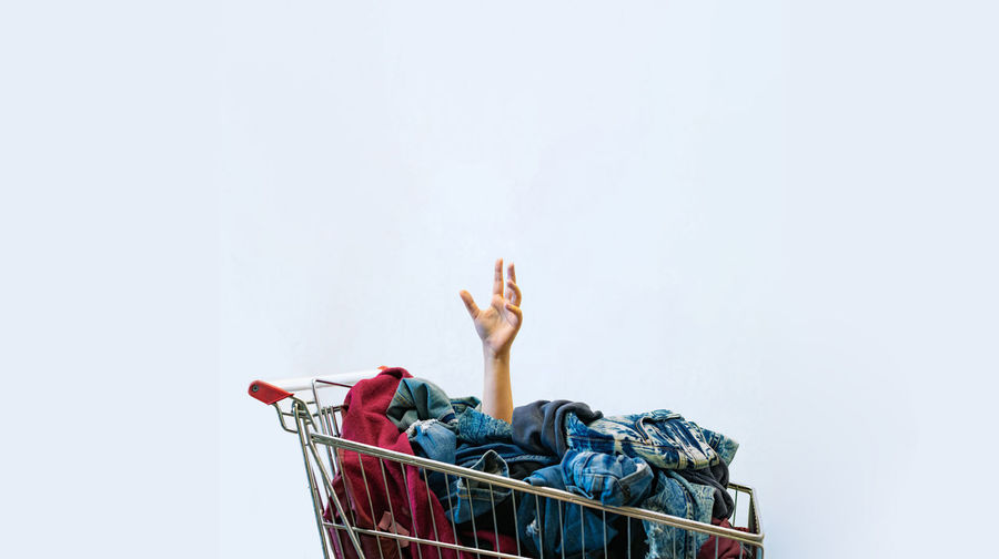 Cropped hand in shopping cart with laundry against white background