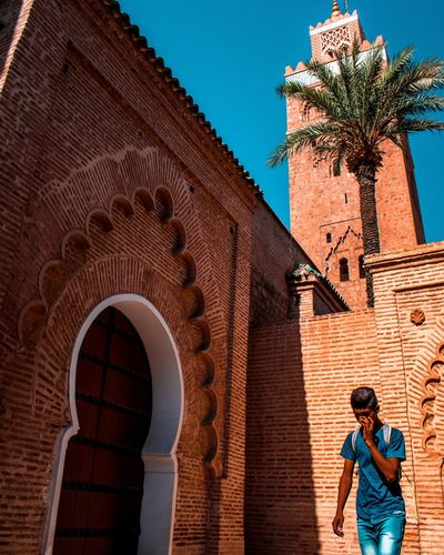 Low Angle View Of Man Standing By Historical Building During Sunny Day
