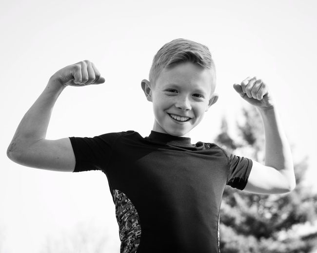 Low Angle Portrait Of Smiling Boy Flexing Muscles While Standing Against Clear Sky