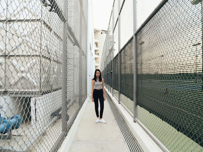 Full length portrait of woman standing on walkway amidst fence