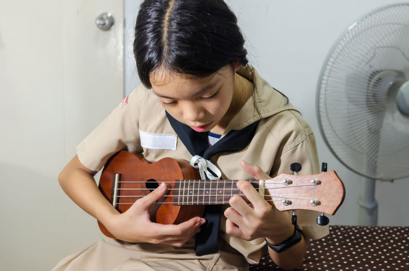 Girl playing small guitar while sitting at home
