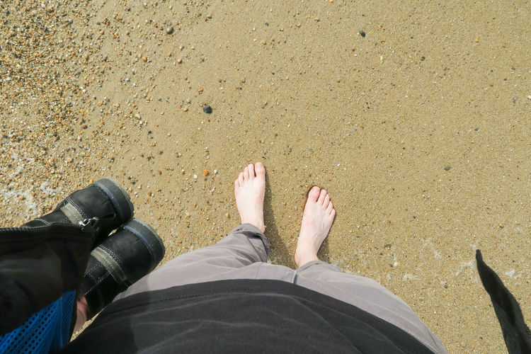 High angle view on legs and barefood feed standing on a sand beach in porto, portugal Beach barefoot Feet Vacation Seaside Low Section Beach Men Standing Human Leg Sand High Angle View Relaxation Personal Perspective Human Foot Stay Out