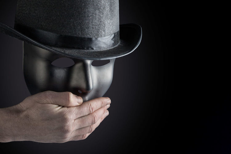 Male hand hiding mouth of black mask wearing black top hat on black background with copy space. Freedom of speech concept Copy Space Isolated Shhh Sign Black Black Background Close-up Concept Conceptual Conceptual Photography  Day Holding Human Body Part Human Hand Indoors  Mask One Person People Shh Studio Shot Top Hat