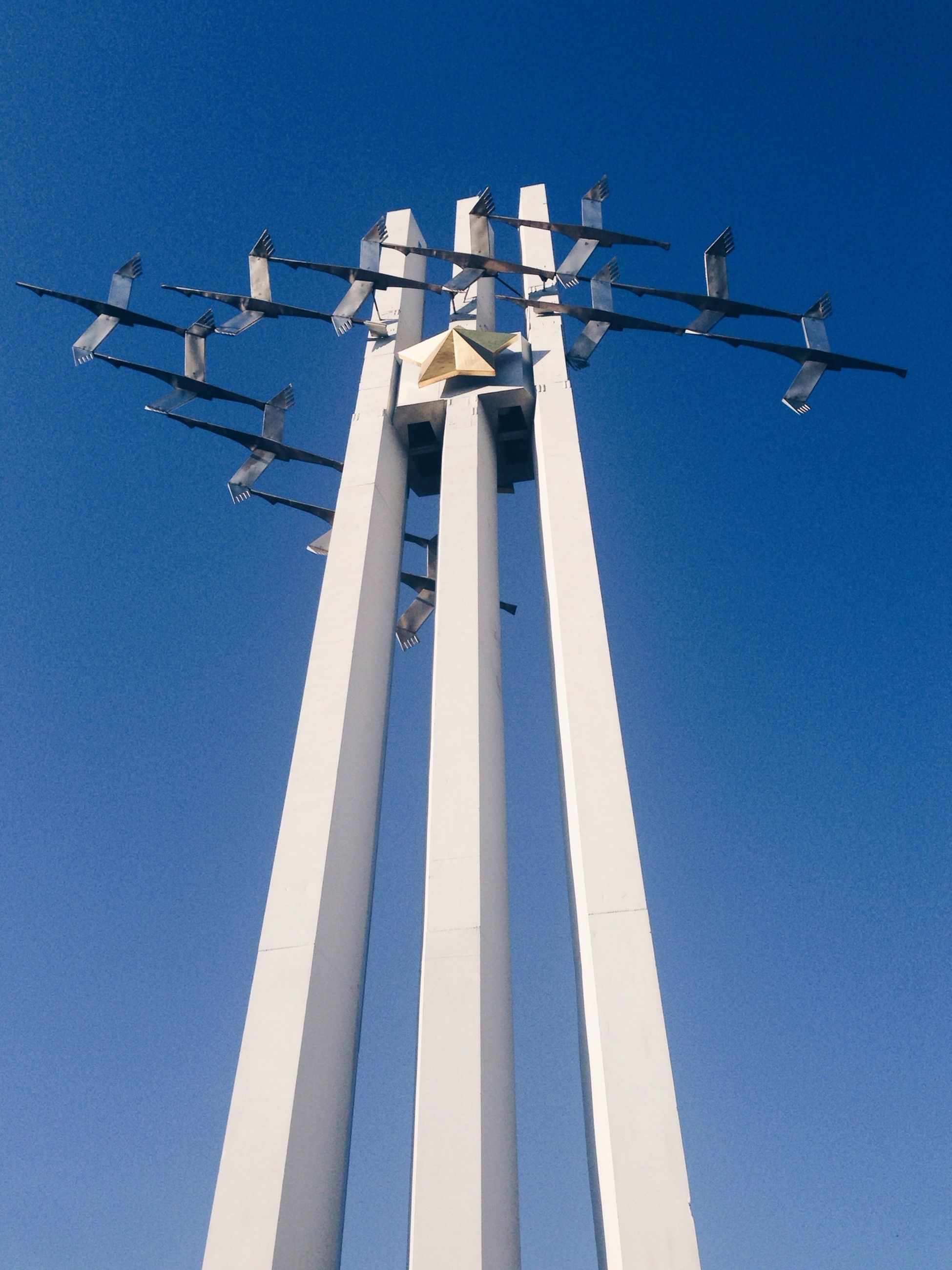 low angle view, blue, clear sky, day, pole, alternative energy, fuel and power generation, environmental conservation, in a row, sky, copy space, wind power, built structure, no people, outdoors, renewable energy, sunlight, wind turbine, cross, religion