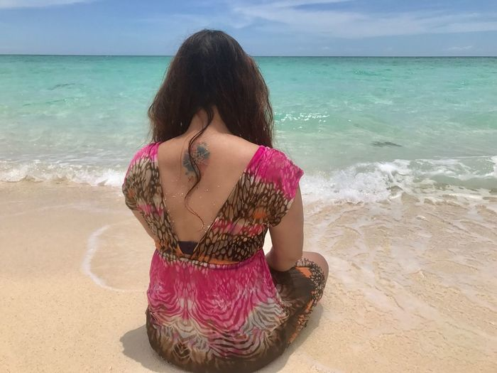 Rear view of tattooed woman sitting at beach against sky on sunny day