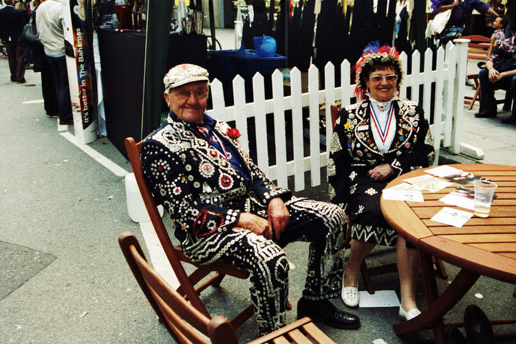 East London Postcode Postcards Casual Clothing Chair Day Full Length Leisure Activity Lifestyles Looking At Camera Outdoors Pearly Kings And Queens Of London Town! People Portrait Real People Sitting Two People Young Adult