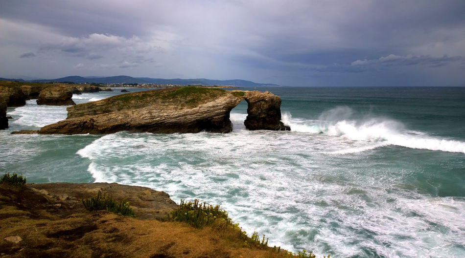 Rock formation at catedrais beach against cloudy sky