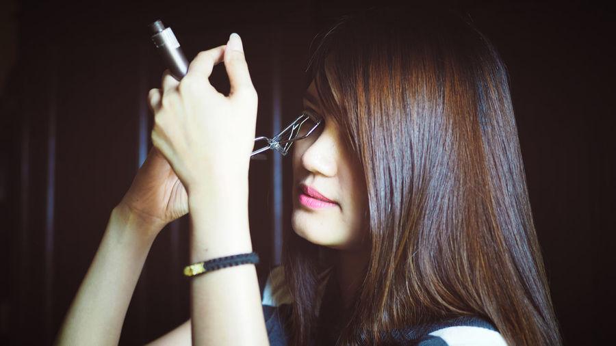 Mid adult woman using eyelash curler at home