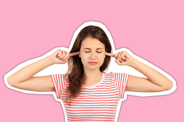 Portrait of a beautiful young woman against pink background