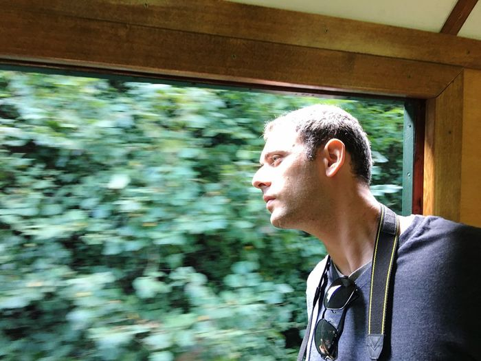 Close-up of young man looking through window in moving train