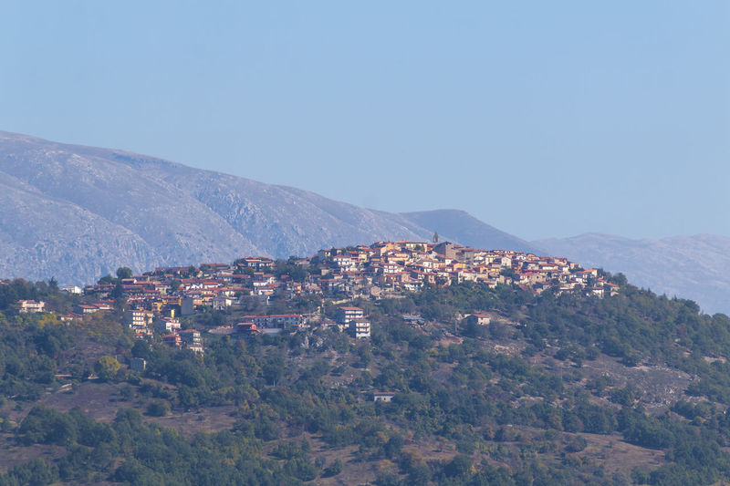 Townscape by mountain against clear sky