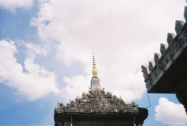 Low angle view of historic temple against cloudy sky