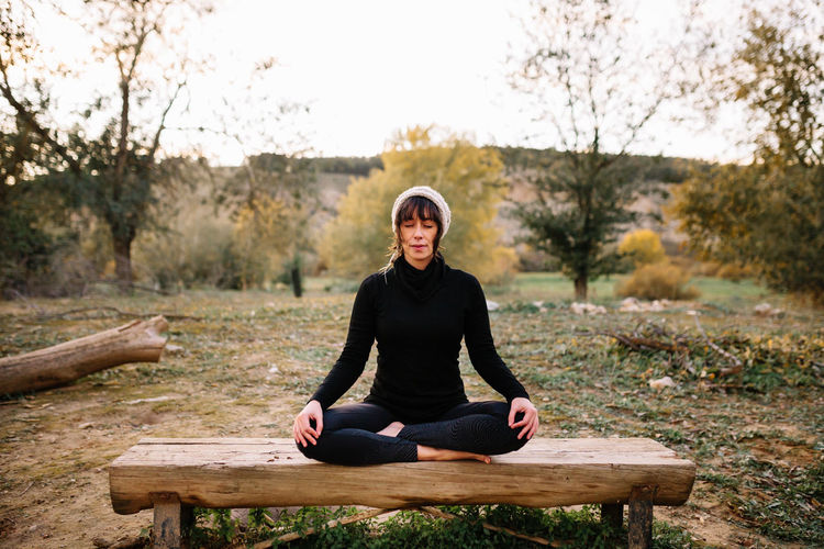 Full length of woman meditating at park