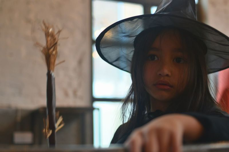 Close-up of girl wearing witch costume at home