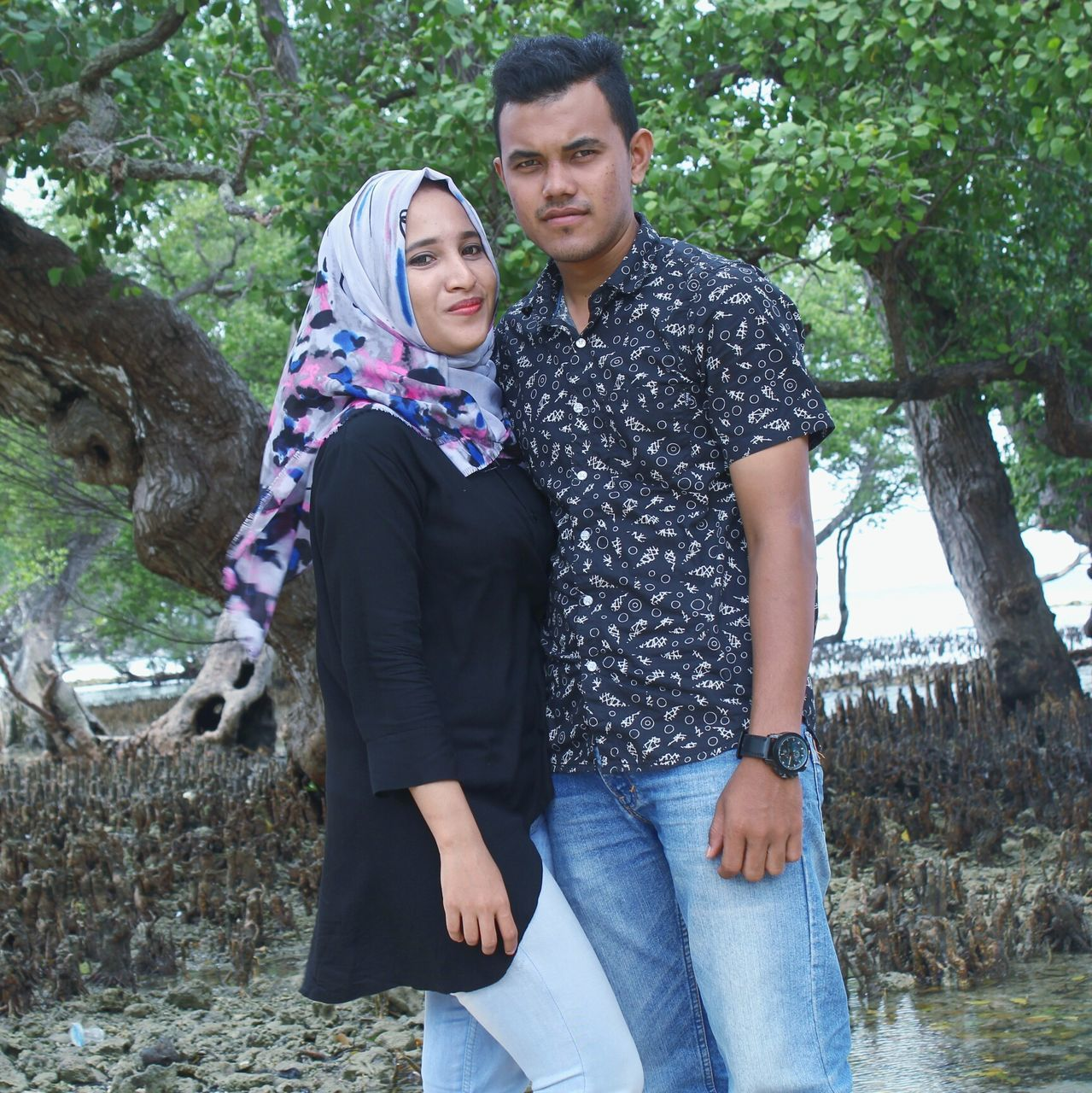 two people, real people, togetherness, young women, love, young men, young adult, front view, leisure activity, casual clothing, tree, couple - relationship, heterosexual couple, day, lifestyles, outdoors, young couple, smiling, happiness, hugging, looking at camera, standing, bonding, nature, posing, beautiful woman, portrait, groom