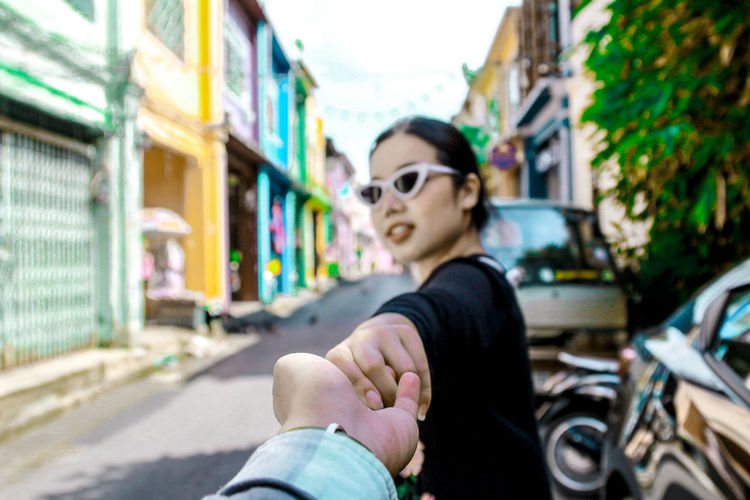 Cropped image of boyfriend holding girlfriend hand in city