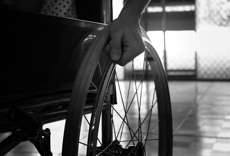 Cropped hand of disabled person on wheel chair